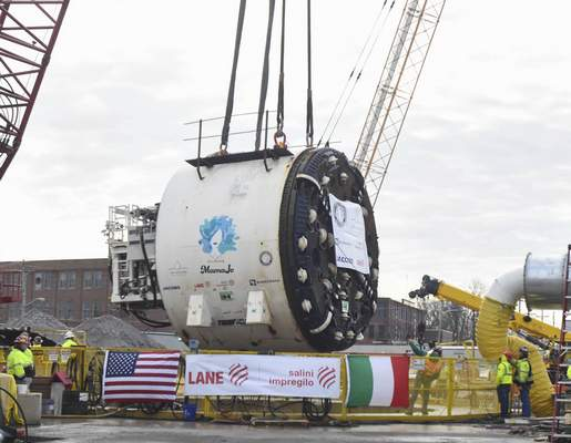 Construction crews watch as the cutterhead for tunnel boring machine MamaJo is lowered into the working shaft of Fort Wayne's deep-rock sewer tunnel.  MamaJo will move 3 feet per hour, five days a week.(Michelle Davies | The Journal Gazette)