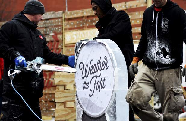 Katie Fyfe | The Journal Gazette  Ice carvers from Parkview come together to carve a Weather the Fortsculptureand several others during the fourth annual Weather the Fort in the Barrett McNagny parking lot on Saturday.