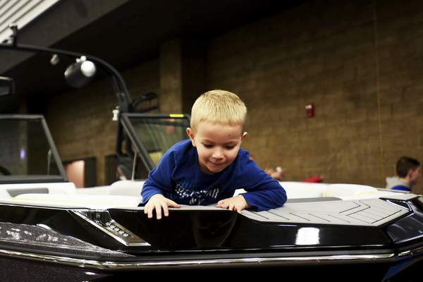Katie Fyfe   The Journal Gazette  Beckett Thiel, 3, checks out a boat during the 38th Fort Wayne Boat Show and Sale at the Allen County War Memorial Coliseum on Sunday.