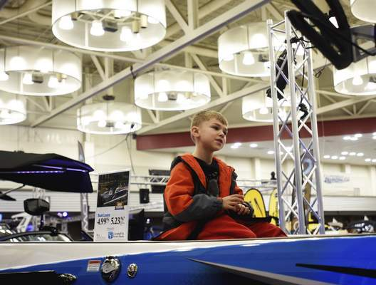 Katie Fyfe   The Journal Gazette  Dane Bowman, 7, hangs out on top of a boat on display during the 38th Fort Wayne Boat Show & Sale at the Allen County War Memorial Coliseum on Sunday.