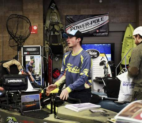 Katie Fyfe   The Journal Gazette  Jaxton Orr with Hobie & Dry Dock shows attendees the Hobie Pro Angler 14 model, one of the many kayaks on display during the 38th Fort Wayne Boat Show and Sale at the Allen County War Memorial Coliseum on Sunday.