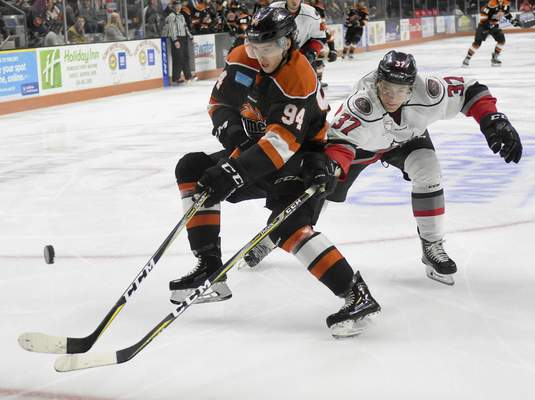 Rachel Von | The Journal Gazette  The Komets' Oskari Halme and the Adirondack Thunder's Desmond Bergin fight for the puck during the second period atMemorial Coliseum on Friday.