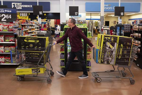 Washington Post Juston Herbert pushes two carts loaded down with Morf Boards, a popular kids toy, through a Walmart in Phoenix.