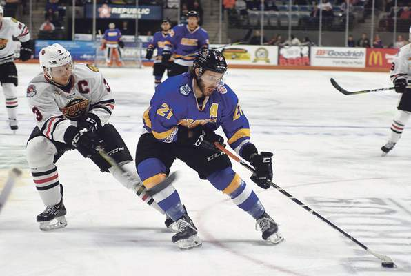 Katie Fyfe | The Journal Gazette: The Komets' Marco Roy, right, tries to maintain the puck during a recent game against Indy.