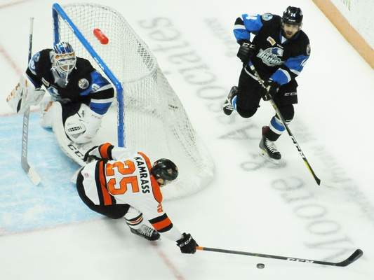 Justin A. Cohn | The Journal Gazette  The Komets' Jake Kamrass, bottom, stretches for the puck as he's chased by the Wichita Thunder's Jakob Stukel, right, as goaltender Dylan Wells, left, looks on Wednesday at Memorial Coliseum.