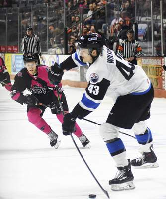 Katie Fyfe | The Journal Gazette  The Komets' Jake Kamrass tries to get the puck from Wichita's Jared Wilson during the first period at Memorial Coliseum on Friday.