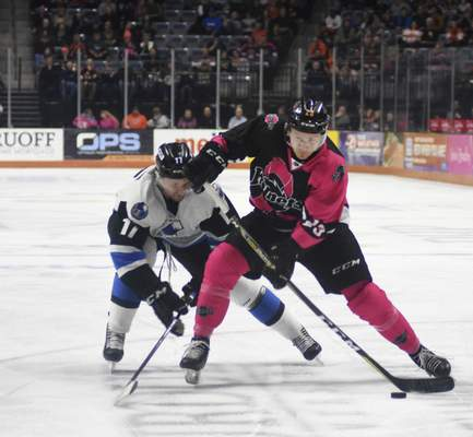 Katie Fyfe | The Journal Gazette  The Komets' Kevin Gibson passes the puck while Wichita's Stefan Fournier tries to stop him during the second period at Memorial Coliseum on Friday.
