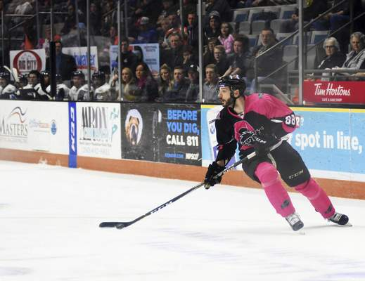 Katie Fyfe | The Journal Gazette  The Komets' Justin Hodgman hits the puck during the second period agianst Wichita Thunder at Memorial Coliseum on Friday.