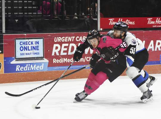 Katie Fyfe | The Journal Gazette  The Komets' Anthony Petruzzelli hits the puck while Wichita's Marc-Oliver Crevier-Mornin tries to stop him during the first period at Memorial Coliseum on Friday.