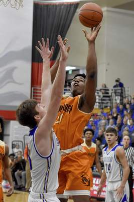 Rachel Von   The Journal Gazette  Northrop's Sydney Curry shoots the ball as East Noble's Brent Cox tries to block the shot in the first quarter of the Boys Basketball Sectional Finals at DeKalb on Saturday.