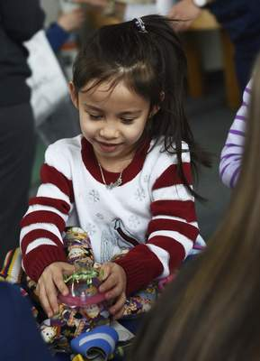 Katie Fyfe | The Journal Gazette  Nancy Ware, 5, plays at the teddy bear first aid station during Doctor's Day at Science Central on Saturday.