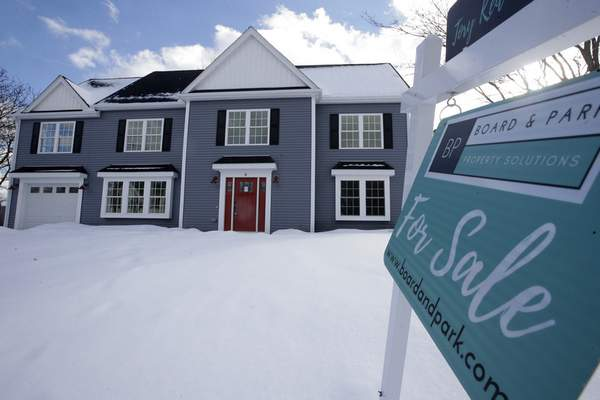 This Thursday, Feb. 21, 2019 photo shows a newly constructed home with a fore sale sign in Natick, Mass. (AP Photo/Steven Senne)