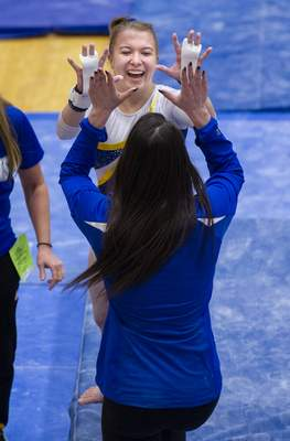 Homestead High School gymnast Catherine Milne celebrates after competing on the bars during competition of the 47th Annual IHSAA Gymnastics State Finals at Noblesville High School in Noblesville, Ind. Saturday, March 9, 2019 . (Doug McSchooler/for Journal-Gazette)