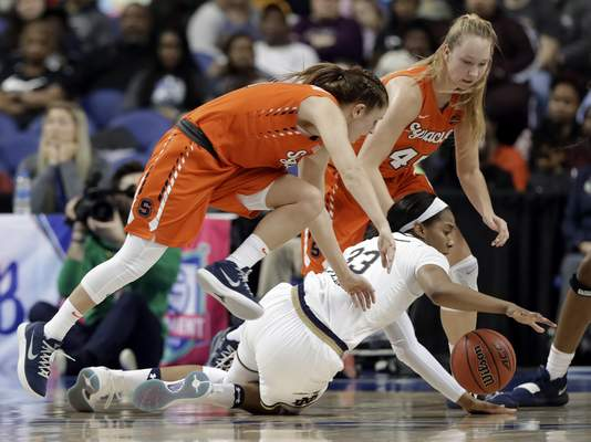 Notre Dame's Danielle Patterson (33) dives for the ball as Syracuse's Digna Strautmane (45) and Tiana Mangakahia defend during the first half of an NCAA college basketball game in the Atlantic Coast Conference women's tournament in Greensboro, N.C., Saturday, March 9, 2019. (AP Photo/Chuck Burton)