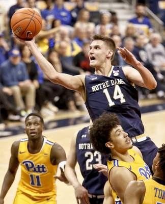 Notre Dame's Nate Laszewski (14) shoots over Pittsburgh's Kene Chukwuka, right, and Sidy N'Dir (11) during the second half of an NCAA college basketball game, Saturday, March 9, 2019, in Pittsburgh. (AP Photo/Keith Srakocic)