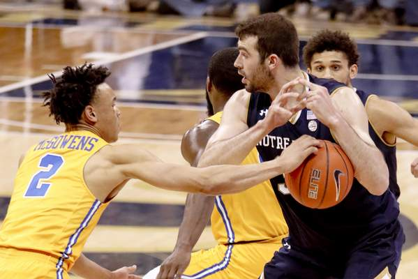 Pittsburgh's Trey McGowens (2) knocks the ball away from Notre Dame's John Mooney and recovered the loose ball with time running out during the second half of an NCAA college basketball game, Saturday, March 9, 2019, in Pittsburgh. Pittsburgh won 56-53. (AP Photo/Keith Srakocic)