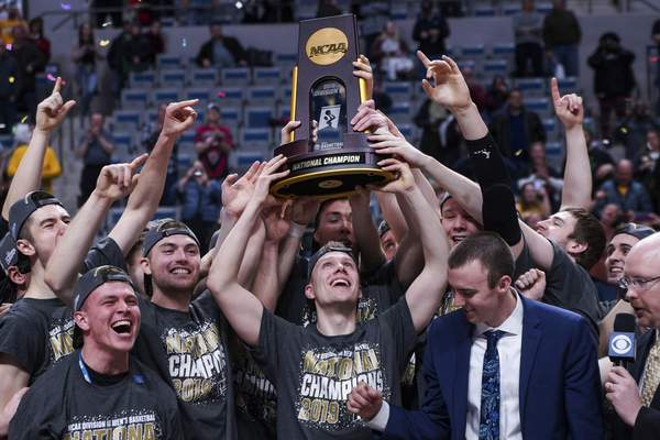 Mike Moore | The Journal Gazette  University of Wisconsin-Oshkosh players hoist the NCAA DivisionIII men's basketball national championship trophy Saturday at Memorial Coliseum.