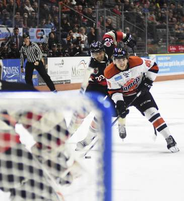 Katie Fyfe | The Journal Gazette  Komets' Phelix Martineau tries to shoot the puck while the Cincinnati Cyclone's Arvin Atwal defends him during the first period at Memorial Coliseum on Friday.