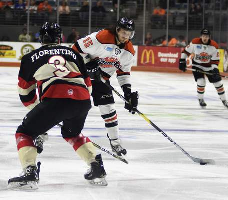 Katie Fyfe | The Journal Gazette  Komets' J.C. Campagna hits the puck while the Cincinnati Cyclone's Anthony Florentino defends him during the first period at Memorial Coliseum on Friday.