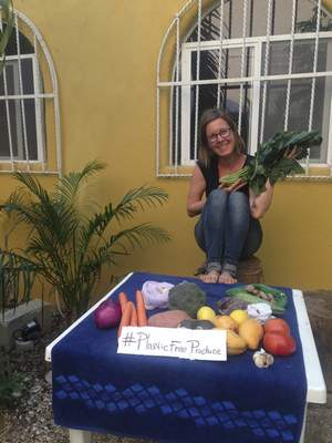 Courtesy  In this March 15, 2018 photo, travel and lifestyle writer Jule Eisendick poses for a photo behind a table advertising the hashtag #plasticfreeproduce to help raise awareness and to show how beautiful plastic free produce looks, while on a trip in Playa Del Carmen, Mexico. Despite constant travel, Eisendick practices a a low to zero food waste life. (Jule Eisendick via AP)