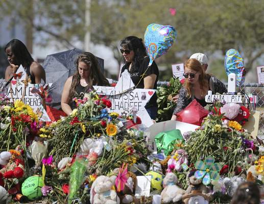 FILE - In this Feb. 25, 2018 file photo, mourners bring flowers as they pay tribute at a memorial for the victims of the shooting at Marjory Stoneman Douglas High School, in Parkland, Fla. (David Santiago/Miami Herald via AP, File)