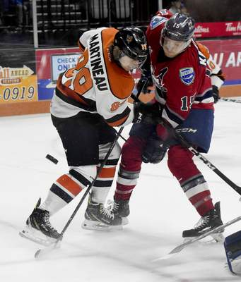 Rachel Von | The Journal Gazette  The Komets' Phelix Martineau and Wings' Eric Kattelus fight for the puck during the first period at the Memorial Coliseum on Wednesday.