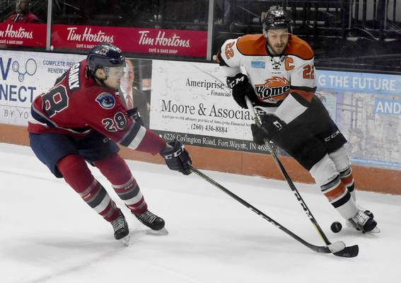 Rachel Von | The Journal Gazette  The Komets' Jamie Schaafsma and Wings' Tyler Ganley fight for the puck during the first period at the Memorial Coliseum on Wednesday.
