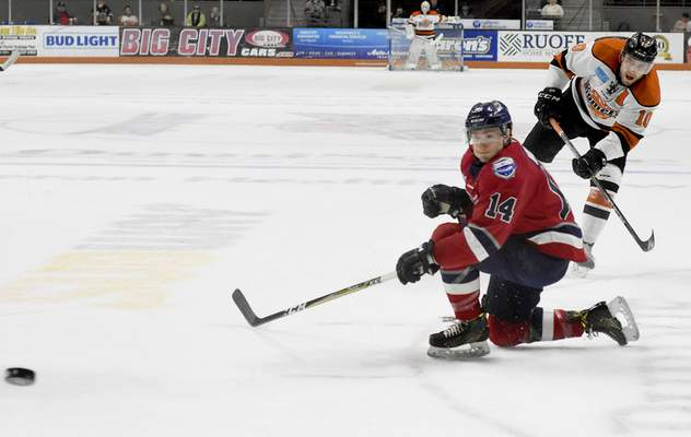 Rachel Von | The Journal Gazette  The Komets' Brady Shaw shoots the puck past Wings' Ben Wilson during the first period at the Memorial Coliseum on Wednesday.