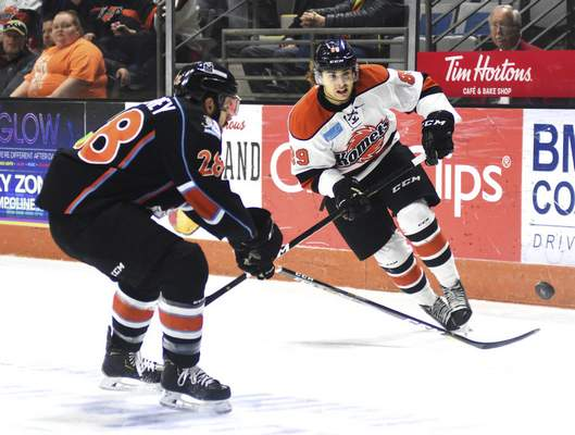 Katie Fyfe | The Journal Gazette  The Komets' Phelix Martineau chases the puck while the Mavericks' Riley Sweeney defends him during the first period at Memorial Coliseum on Saturday.