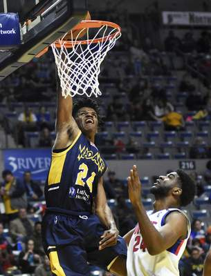 Katie Fyfe | The Journal Gazette  Mad Ants' Alize Johnson dunks the ball while Grand Rapids Drive's Johnny Hamilton tries to block him during the third quarter at Memorial Coliseum on Saturday.