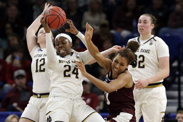 Notre Dame's Arike Ogunbowale (24) grabs a rebound against Texas A&M's Aja Ellison (0) during the second half of a regional semifinal game in the NCAA women's college basketball tournament, Saturday, March 30, 2019, in Chicago. (AP Photo/Nam Y. Huh)