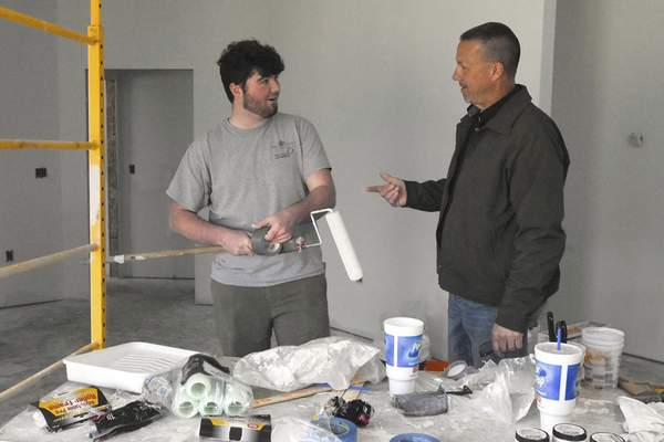 Photos by Michelle Davies | The Journal Gazette Garrett High School junior Tristan Thomas speaks with Chad Sutton,  director of the career development program at Garrett High School, in one of the homes students are building.