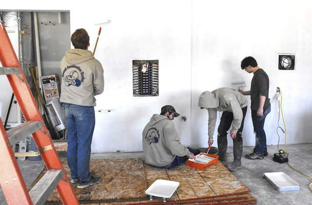 Michelle Davies | The Journal Gazette  Garrett High School students in the career development program prime the garage walls of a home that the students built in the Baltimore Place subdivision.