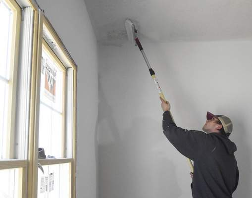 Michelle Davies | The Journal Gazette  Isaac King, a junior at Garrett High School, paints the ceiling of the master bedroom of a home that students in the career development program built in theBaltimore Place subdivision.