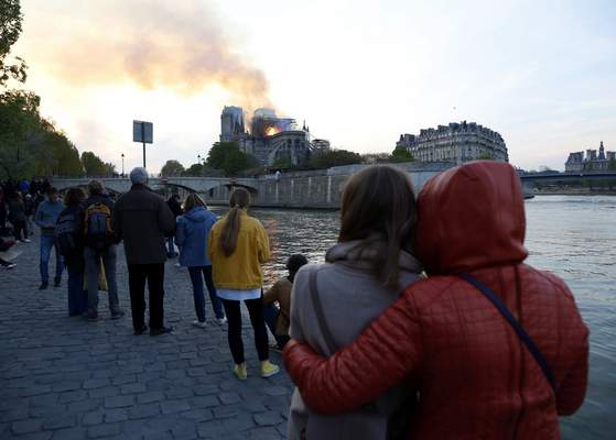 "People watch as flames and smoke rise from the cathedral. ""This is a historic moment for all of us, in the worst possible sense of the term,"" 35-year-old onlooker Donia Hammami said.  (Associated Press photos)"