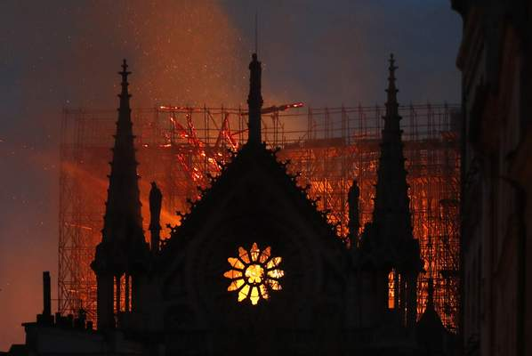 Massive plumes of yellow brown smoke fill the air above Notre Dame Cathedral on Monday and ash falls around the island that marks the center of Paris.