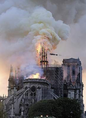 Flames and smoke rise as the spire on Notre Dame Cathedral collapses Monday in Paris. Early reports say the fire was started by renovations at the centuries-old cathedral.