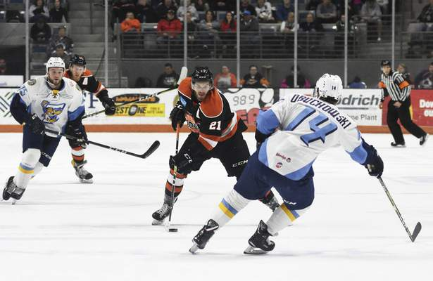 Katie Fyfe | The Journal Gazette Komets' Marco Roy hits the puck while Toledo Walleye's Ryan Obuchowski defends him during the first period at Memorial Coliseum in Fort Wayne on Friday April 19th, 2019.