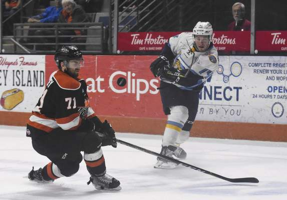 Michelle Davies | The Journal Gazette Toledo's Ryan Obuchowski takes a shot on goal in the second period of Wednesday's game around the Komets' Ryan Lowney.