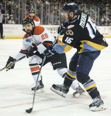 Jeremy Wadsworth | The Blade  Toledo Walleye forward Bryan Moore takes a shot againstKomets defenseman Chase Stewart during the first period of Game 5 of the Central Division semifinals at the Huntington Center in Toledo, Ohio.