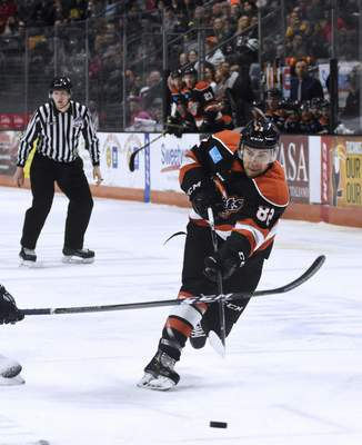 Katie Fyfe | The Journal Gazette  The Komets' Anthony Nellis hits the puck during the first period against the Toledo Walleye at Memorial Coliseum on Friday.