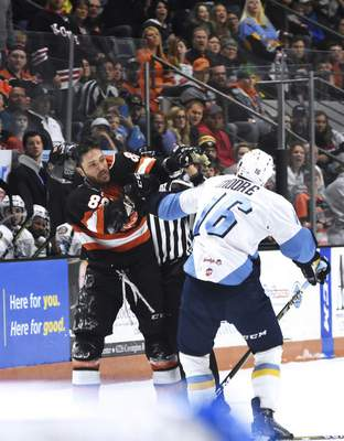 Katie Fyfe | The Journal Gazette  The Komets' Justin Hodgman and Toledo Walleye's Bryan Moore get into a fight during the first period at Memorial Coliseum on Friday.