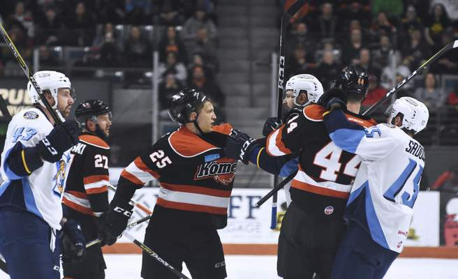Katie Fyfe | The Journal Gazette  The Komets' Jake Kamrass gets held by Toledo Walleye during a fight during the first period at Memorial Coliseum on Friday.