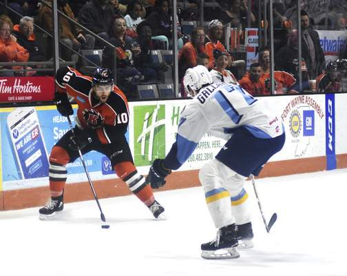 Katie Fyfe | The Journal Gazette  Komets' Brady Shaw carries the puck while Toledo Walleye's Zach Gallant defends him during the second period at Memorial Coliseum on Tuesday.