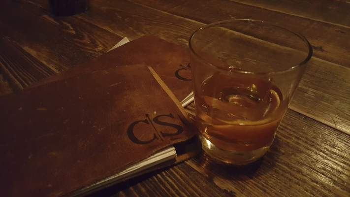 Leather drink menus flanked by a smoked old fashioned at Copper Spoon in The Harrison.