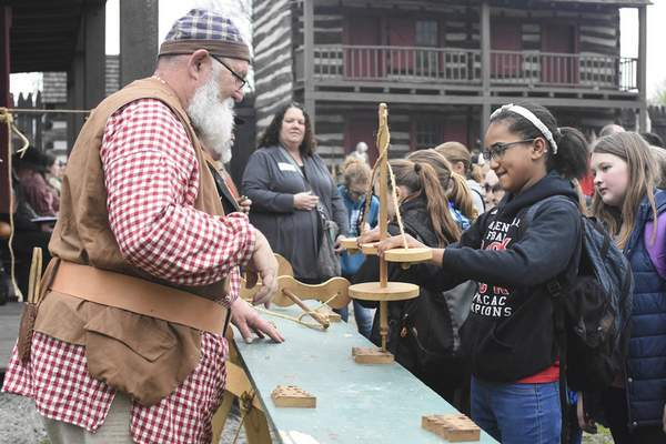 Michelle Davies | The Journal Gazette  Reenactor Dennis Dix watches as Adams Central fifth grader Kailyn Steiner tries out the pump drill, a multipurpose tool used for both drilling and making fire, Friday morning at the Historic Old Fort's Education Day.