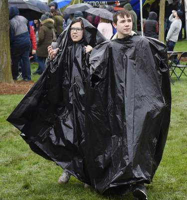 Rachel Von | The Journal Gazette  Hannah Gugel, left, and Brandon Daileystay drywith a couple of garbage bags turned into ponchos during the Michiana Wine Festival at Headwaters Park on Saturday.