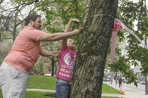 Michelle Davies | The Journal Gazette  Brandon Young and his daughter Aubrey, 10, both of Fort Wayne, tie a pink ribbon around a tree in Freimann Square Friday morning. The pink ribbons are part of Paint the Town Pink, a monthlong campaign of fundraising and awareness for the Vera Bradley Foundation. Young said that his daughter has waited to be able to participate in the event and that she finally understands the importance of the more than 1,000 ribbons thathave been hung.