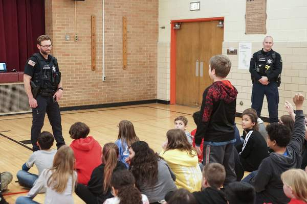 Mike Moore | The Journal Gazette  Fourth grader Connor Landquist stands to answer officer James Arnold's question about bike safety during a presentation to prepare students for Bike to School Day next week at Price Elementary School on Wednesday.
