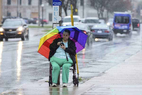 Mike Moore | The Journal Gazette Lola Johnson sits under an umbrella in the rain while waiting for her bus on Monday.